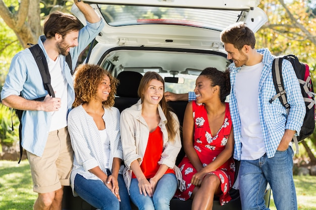 Группа друзей в поездке, сидя в багажнике автомобиля