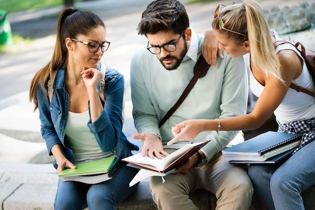 Группа друзей или студентов университета улыбаются, готовятся к экзамену на открытом воздухе