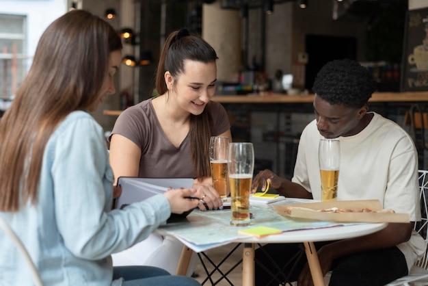カフェでの旅行を計画している友人のグループ 無料写真
