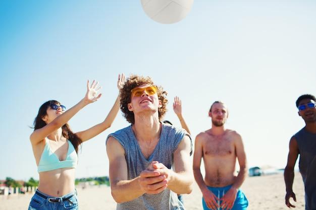 ビーチでビーチバレーで遊んでいる友達のグループ