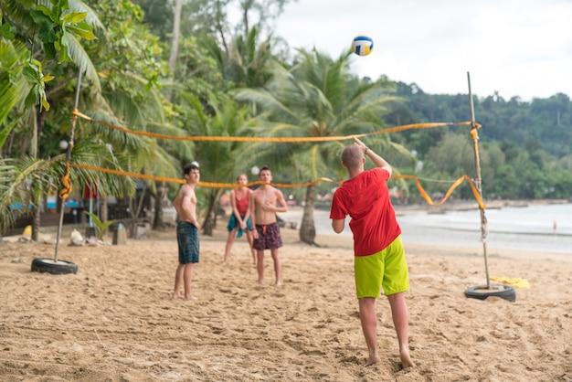 Группа друзей, играющих в пляжный волейбол - многоэтническая группа людей, веселящихся на beac