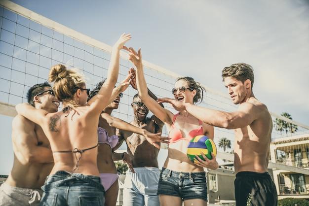 Группа в составе друзья играя пляжный волейбол на пляже.