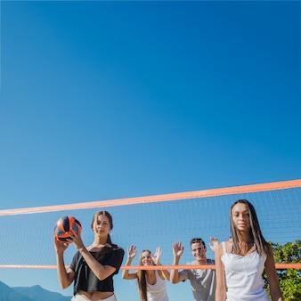 Группа друзей, играющих в пляжный волейбол