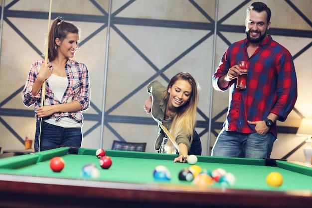 Группа друзей играет в бильярд