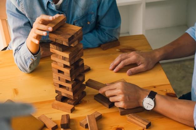 Группа друзей, играющих в деревянные блоки, игра на столе, сложенная головоломка, держащая блоки из дерева, игра планирование рисков и стратегии в бизнесе