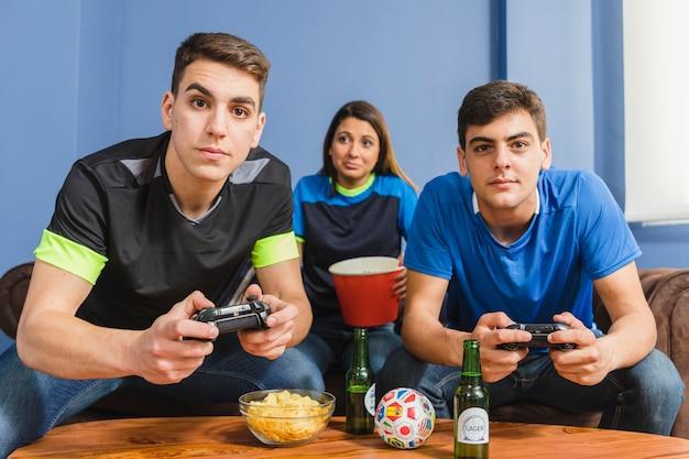 Группа друзей, играющих на консоли