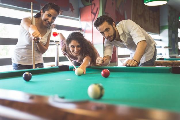 Группа друзей, играющих в бильярд