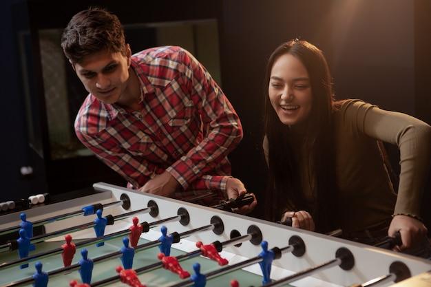 Группа друзей, играющих в настольный футбол в пивном пабе