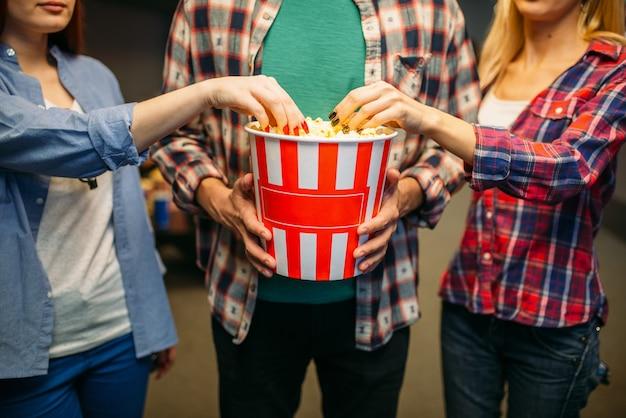 Группа друзей позирует с попкорном в кинозале