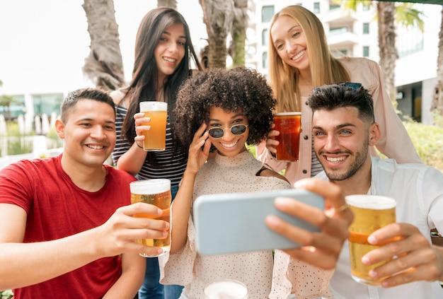 Группа друзей позирует для селфи с пинтами холодного пива, поднимая бокалы в тосте перед камерой на мобильном телефоне со счастливыми улыбками