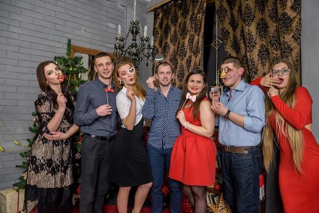 Группа друзей, позирующих в новогодней студии