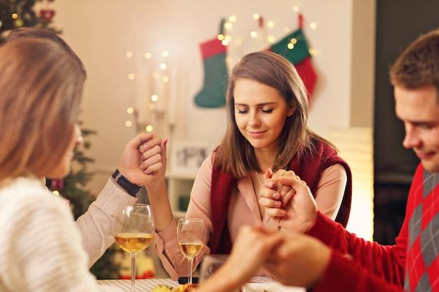 クリスマスのテーブルの上で祈る友人のグループ