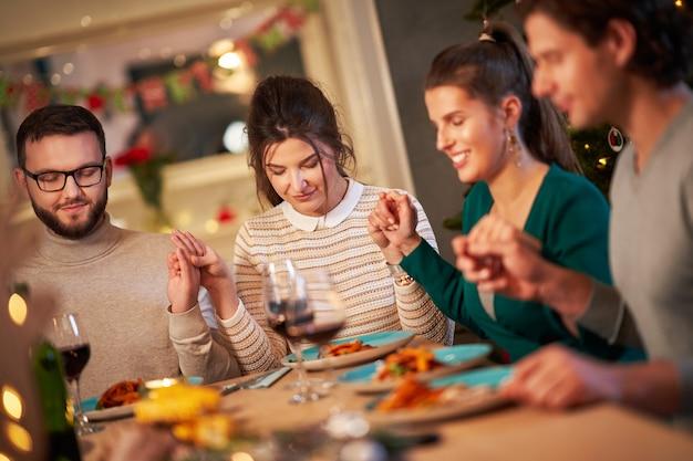 自宅で感謝祭のクリスマステーブルを祈る友人のグループ