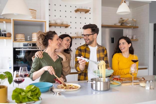 キッチンで食事を準備している友人のグループ