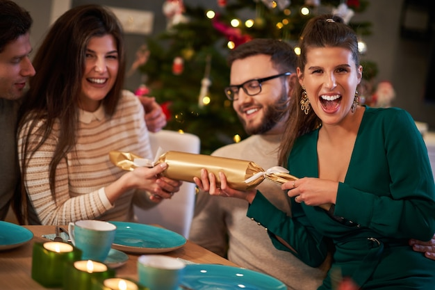 家でクリスマスクラッカーを引っ張る友人のグループ