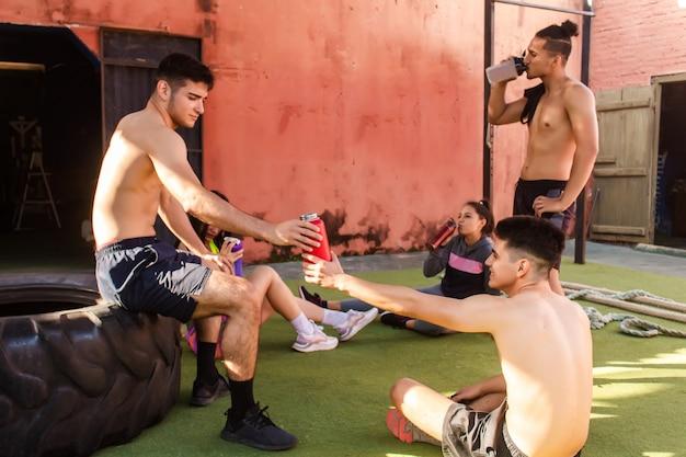 Группа друзей отдыхает, болтает после тренировки во дворе спортзала.