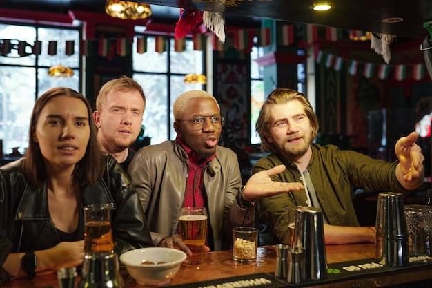 Группа друзей, сидящих за столом с пивом и смотрящих что-то в пабе