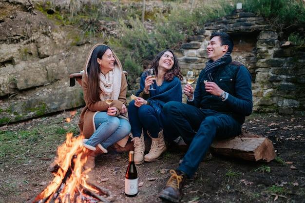 たき火の前でワインを飲みながら話したり笑ったりしている友人のグループ。一体感、友情の概念。