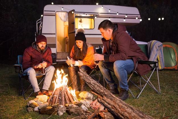 山の秋の寒い夜にキャンプファイヤーの周りに一緒に座っている友人のグループ。電球付きのレトロなキャンピングカー。