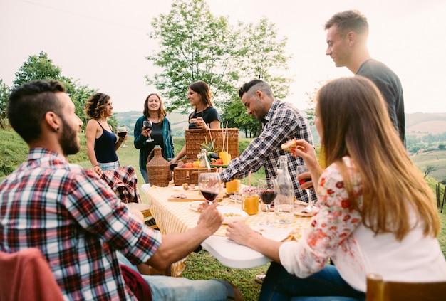 ピクニックやバーベキューを作る時間を過ごす友人のグループ