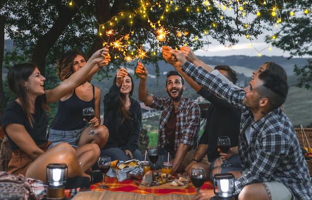 Группа друзей, проводящих время, устраивая пикник и барбекю