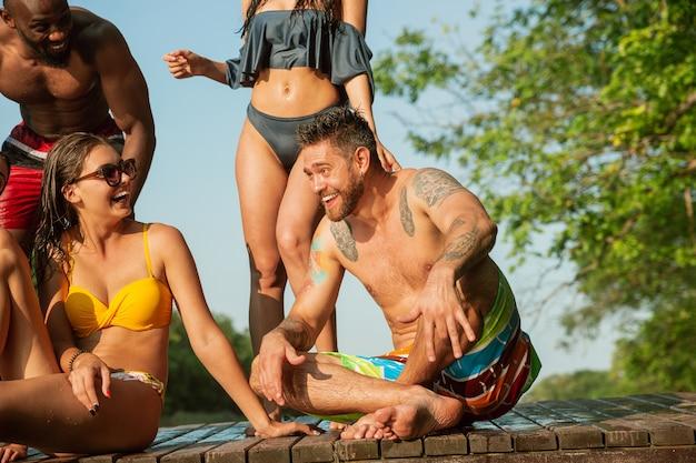 水をはね、川の桟橋で笑っている友人のグループ