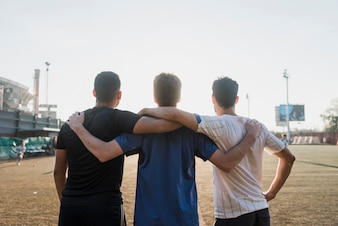 Group of friends standing together facing stadium