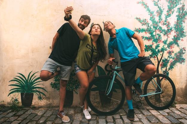 友人のグループが路上で携帯電話で自分撮りをするcopyspacelifestyle