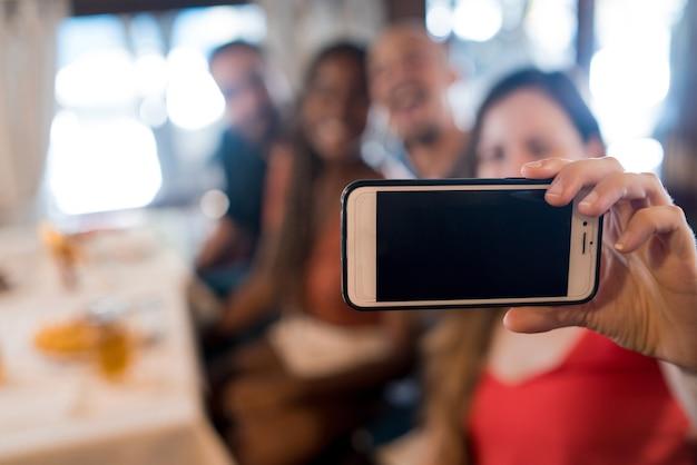 レストランで携帯電話で自分撮りをしている友達のグループ。