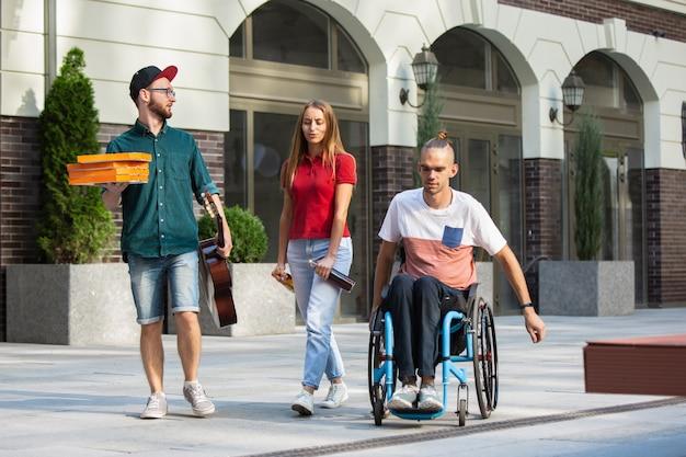 夏の日に街の通りを散歩している友人のグループ