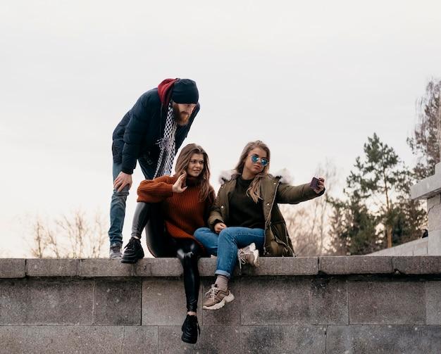 屋外で自分撮りをしている友達のグループ