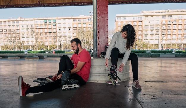 彼らがスケートをする準備をしている間、楽しく話している友人のグループ