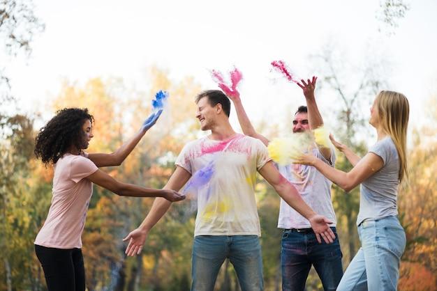 粉の色を空に投げる友人のグループ