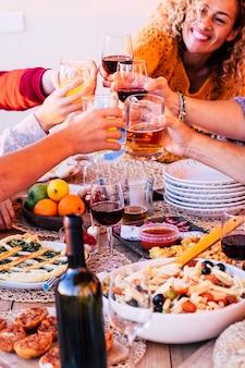友人のグループが乾杯し、ワインとオレンジ ジュースのグラスで一緒に楽しんで友情を楽しんでいる