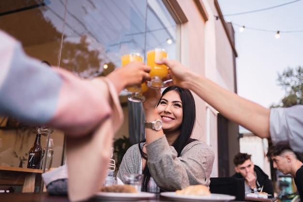 フルーツジュースで乾杯する友人のグループ。