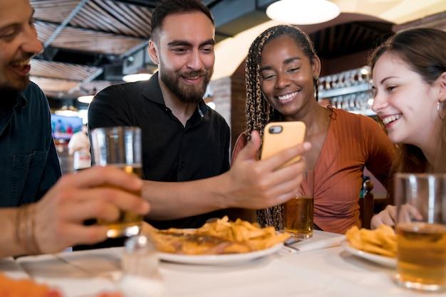 レストランで携帯電話を使用している友人のグループ。