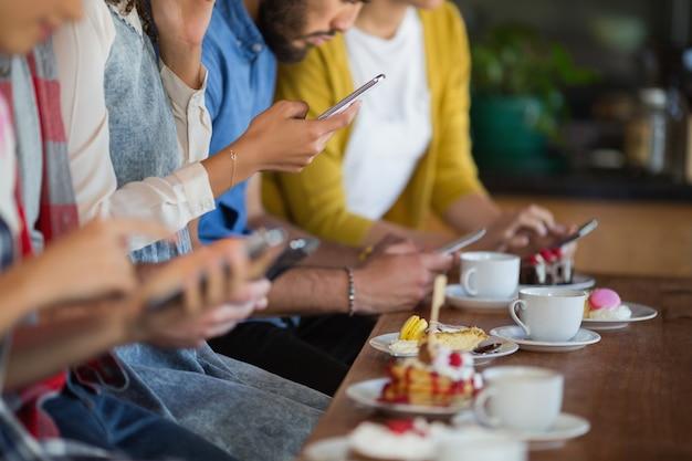 テーブルに座って携帯電話を使用して友人のグループ
