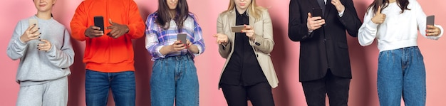 モバイルスマートフォンを使用している友人のグループ。新しいテクノロジーのトレンドに対するティーンエイジャーの中毒。閉じる。ミレニアル世代は、スクロール、ニュースの閲覧、ビデオの視聴、オンラインショッピングを行っています。デバイスとの接続。