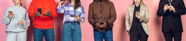 モバイルスマートフォンを使用している友人のグループ。新しいテクノロジーのトレンドに対するティーンエイジャーの中毒。閉じる。