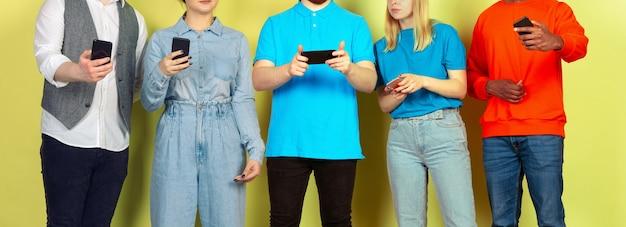 モバイルスマートフォンを使用している友人のグループティーンエイジャーの新しいテクノロジーのトレンドへの依存がクローズアップ