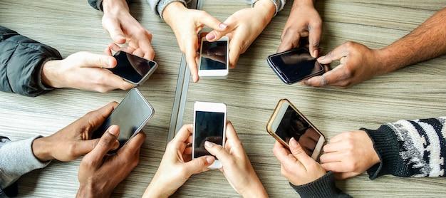 スマートフォンを使用して友人のグループ。携帯電話を楽しんでいる人の手のビュー
