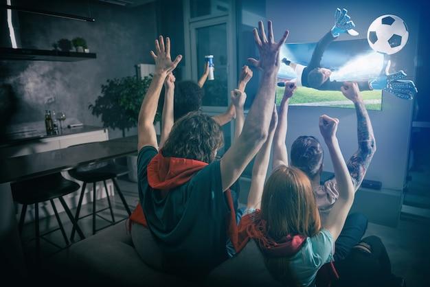 友達のグループがテレビで一緒にゲームを見て喜ぶ