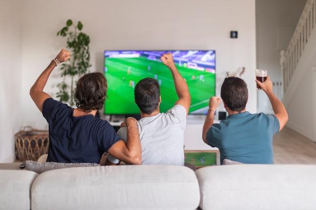 Группа друзей смотрит игру по телевизору, празднуя победу своей команды