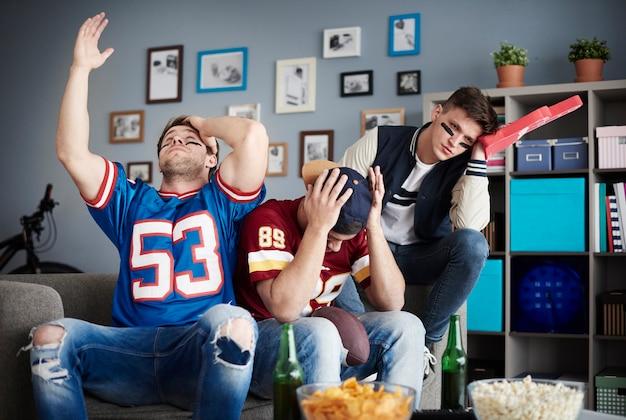 家でサッカーを見ている友達のグループ