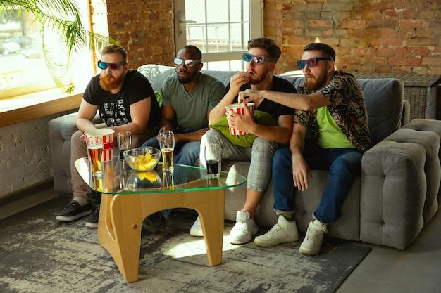 Группа друзей, смотрящих игру по телевизору дома.