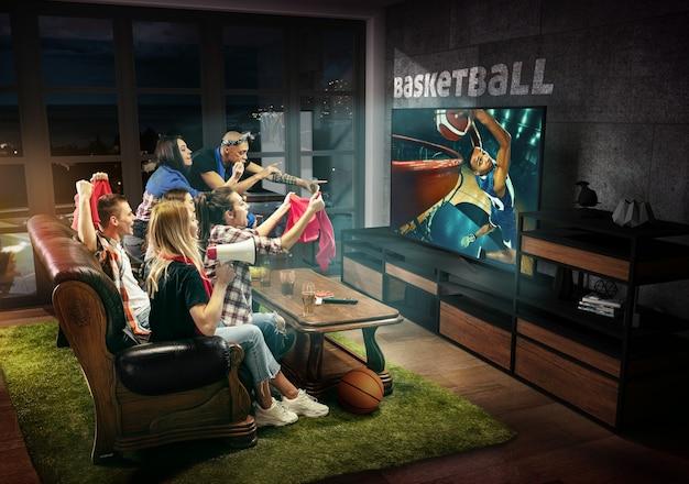 Группа друзей смотрит телевизор, матч, чемпионат, спортивные игры. эмоциональные мужчины и женщины болеют за любимую баскетбольную команду, смотрят на забитый гол. понятие дружбы, соревнования, эмоций.