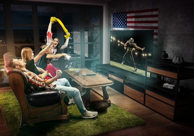 Tv, 경기, 챔피언십, 스포츠 게임을 시청하는 친구들. 깃발을 들고 미국이 가장 좋아하는 축구팀을 응원하는 감정적인 남녀. 우정, 스포츠, 경쟁, 감정의 개념.