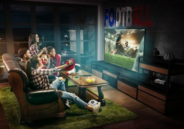 テレビ、試合、選手権、スポーツゲームを見ている友人のグループ。国旗でフランスのお気に入りのサッカーチームを応援する感情的な男性と女性。友情、競争、感情の概念。