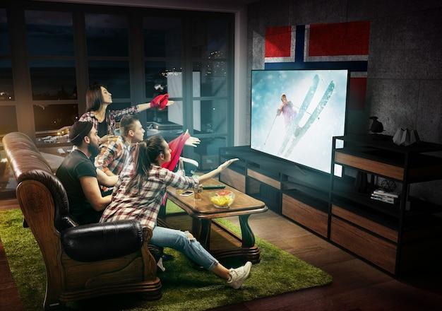 テレビの試合のチャンピオンシップのスポーツゲームを見ている友人のグループ