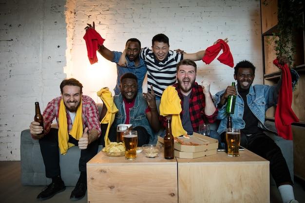 テレビスポーツを見ている友人のグループは、友情の余暇活動の感情のエキサイティングなゲームの概念で見ているお気に入りのチームを応援している感情的なファンを一緒にマッチさせます